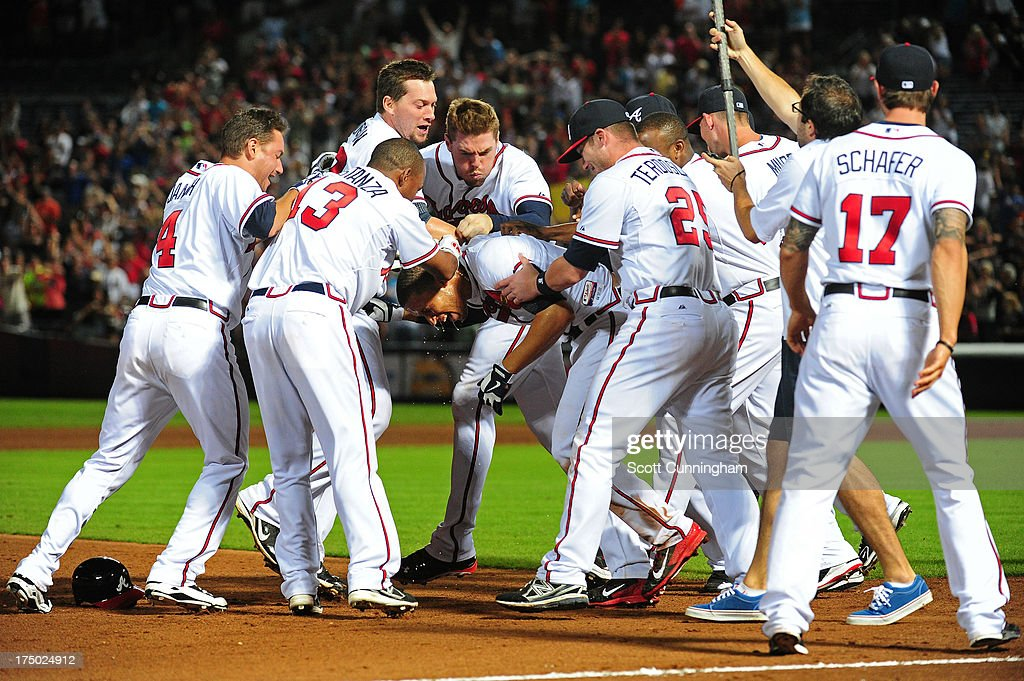 <a gi-track='captionPersonalityLinkClicked' href=/galleries/search?phrase=Andrelton+Simmons&family=editorial&specificpeople=8978424 ng-click='$event.stopPropagation()'>Andrelton Simmons</a> #19 of the Atlanta Braves is mobbed by teammates after knocking in the game-winning run against the Colorado Rockies at Turner Field on July 29, 2013 in Atlanta, Georgia.
