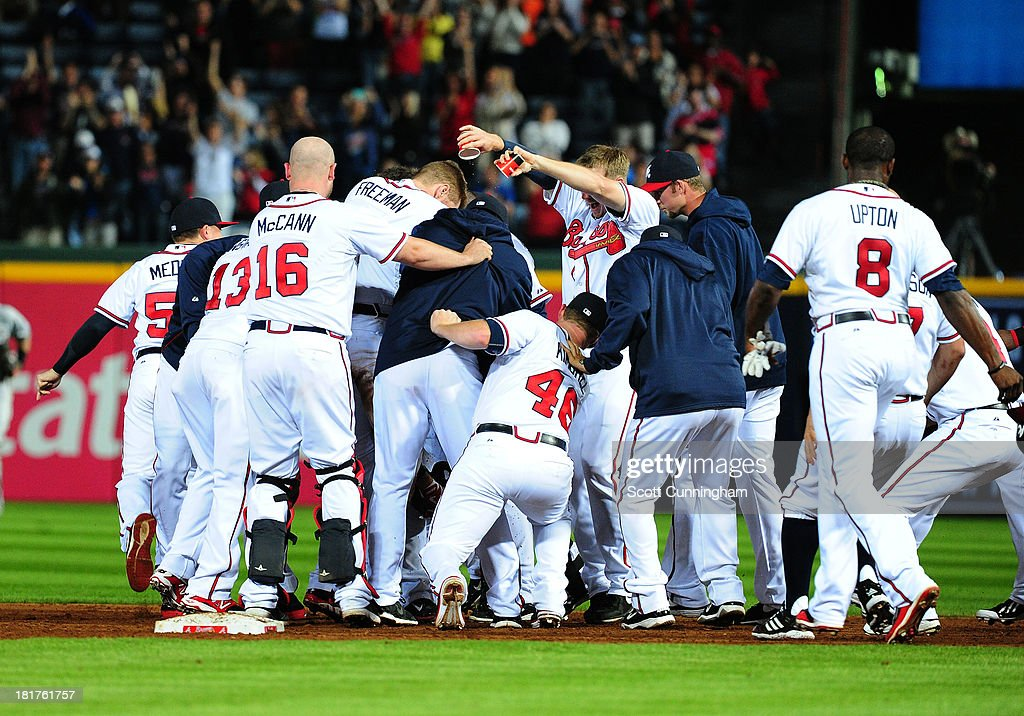 <a gi-track='captionPersonalityLinkClicked' href=/galleries/search?phrase=Andrelton+Simmons&family=editorial&specificpeople=8978424 ng-click='$event.stopPropagation()'>Andrelton Simmons</a> #19 of the Atlanta Braves (obscured) is mobbed by teammates after knocking in the game-winning run in the 9th inning against the Milwaukee Brewers at Turner Field on September 24, 2013 in Atlanta, Georgia.