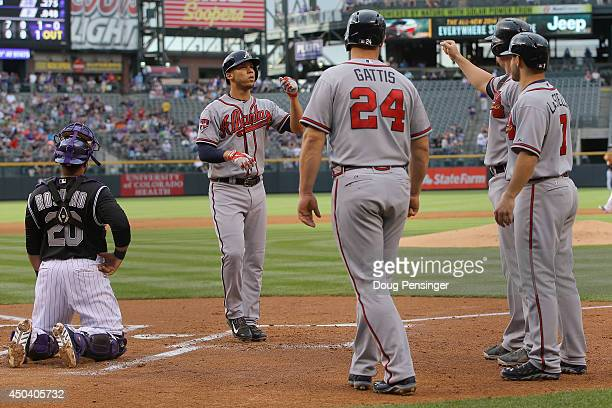 Andrelton Simmons of the Atlanta Braves is welcomed home after his grand slam home run off of starting pitcher Juan Nicasio of the Colorado Rockies...