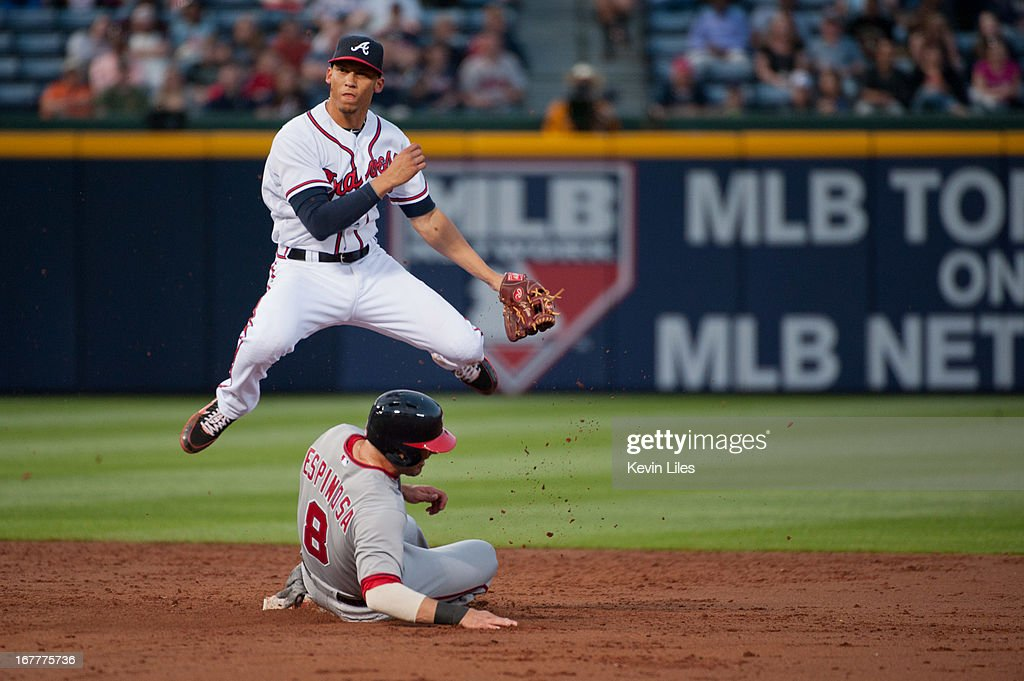 <a gi-track='captionPersonalityLinkClicked' href=/galleries/search?phrase=Andrelton+Simmons&family=editorial&specificpeople=8978424 ng-click='$event.stopPropagation()'>Andrelton Simmons</a> #19 of the Atlanta Braves jumps over <a gi-track='captionPersonalityLinkClicked' href=/galleries/search?phrase=Danny+Espinosa&family=editorial&specificpeople=4410764 ng-click='$event.stopPropagation()'>Danny Espinosa</a> #8 of the Washington Nationals during a double play in the third inning at Turner Field on April 29, 2013 in Atlanta, Georgia. The Braves defeated the Nationals 3-2.
