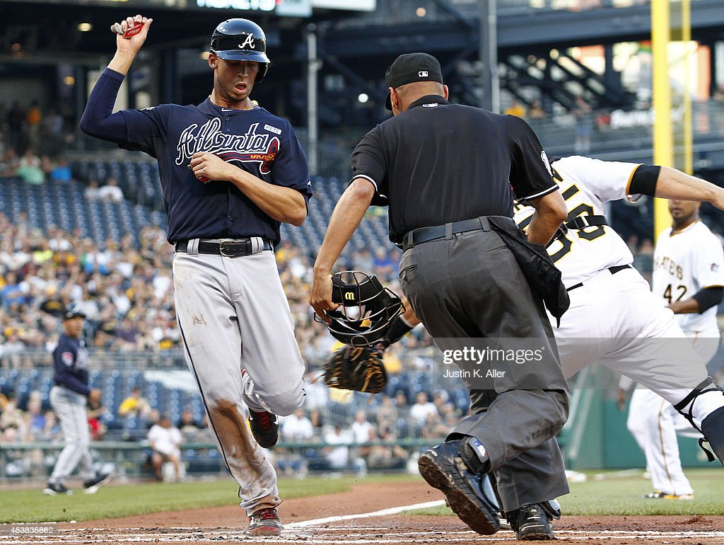 <a gi-track='captionPersonalityLinkClicked' href=/galleries/search?phrase=Andrelton+Simmons&family=editorial&specificpeople=8978424 ng-click='$event.stopPropagation()'>Andrelton Simmons</a> #19 of the Atlanta Braves scores on a RBI single past <a gi-track='captionPersonalityLinkClicked' href=/galleries/search?phrase=Russell+Martin+-+Baseball+Player&family=editorial&specificpeople=13764024 ng-click='$event.stopPropagation()'>Russell Martin</a> #55 of the Pittsburgh Pirates in the second inning during the game at PNC Park on August 19, 2014 in Pittsburgh, Pennsylvania.