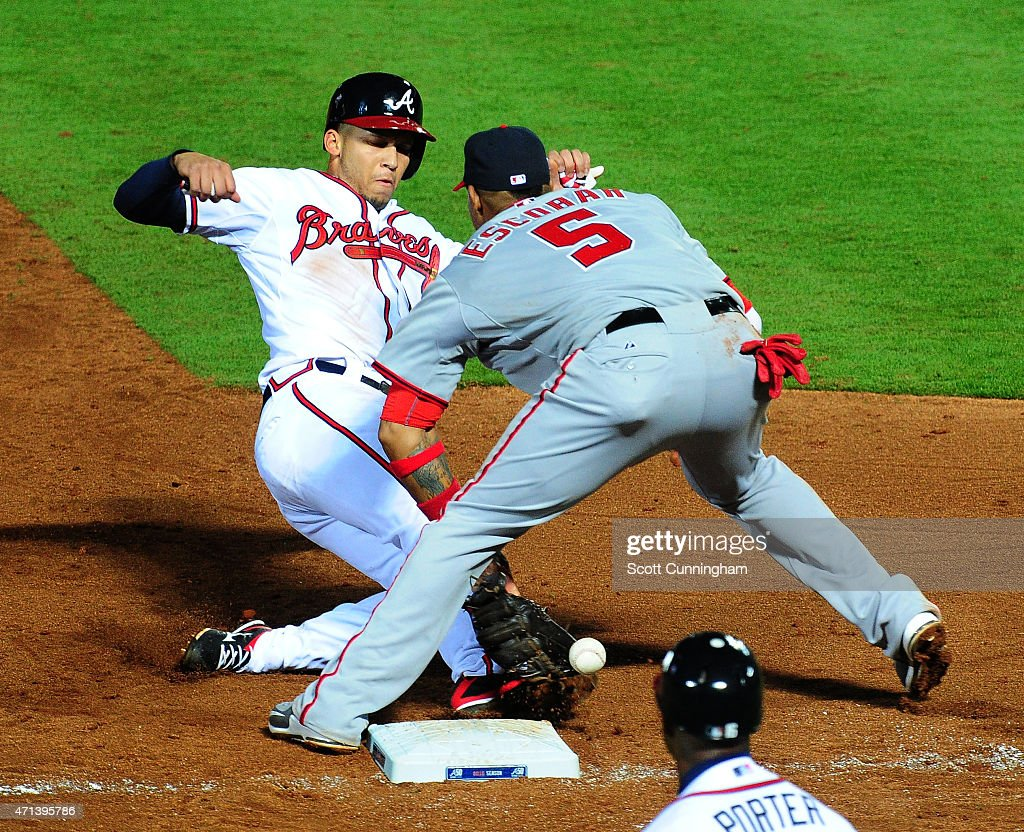 <a gi-track='captionPersonalityLinkClicked' href=/galleries/search?phrase=Andrelton+Simmons&family=editorial&specificpeople=8978424 ng-click='$event.stopPropagation()'>Andrelton Simmons</a> #19 of the Atlanta Braves slides in safely to third base during the fifth inning against <a gi-track='captionPersonalityLinkClicked' href=/galleries/search?phrase=Yunel+Escobar&family=editorial&specificpeople=757358 ng-click='$event.stopPropagation()'>Yunel Escobar</a> #5 of the Washington Nationals at Turner Field on April 27, 2015 in Atlanta, Georgia.