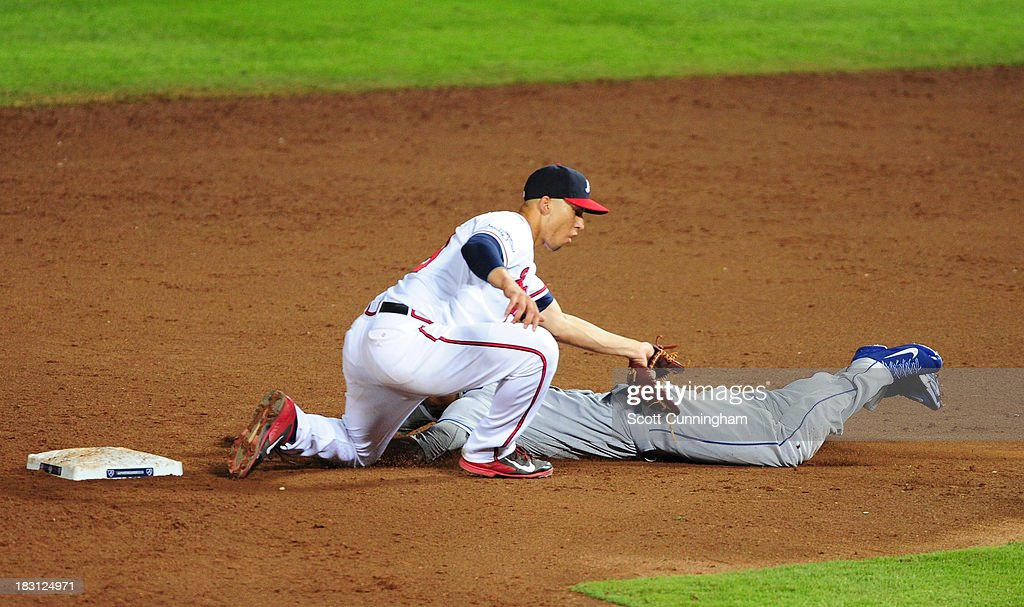 <a gi-track='captionPersonalityLinkClicked' href=/galleries/search?phrase=Andrelton+Simmons&family=editorial&specificpeople=8978424 ng-click='$event.stopPropagation()'>Andrelton Simmons</a> #19 of the Atlanta Braves tags out <a gi-track='captionPersonalityLinkClicked' href=/galleries/search?phrase=Dee+Gordon&family=editorial&specificpeople=7091343 ng-click='$event.stopPropagation()'>Dee Gordon</a> #9 of the Los Angeles Dodgers as he attempts to steal second base in the ninth inning during Game Two of the National League Division Series at Turner Field on October 4, 2013 in Atlanta, Georgia.