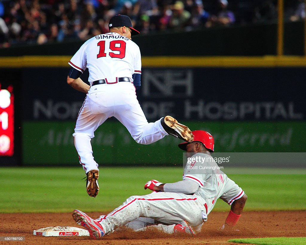 Andrelton Simmons #19 of the Atlanta Braves turns a double play against Domonic Brown #9 of the Philadelphia Phillies during the ninth inning at Turner Field on June 17, 2014 in Atlanta, Georgia.