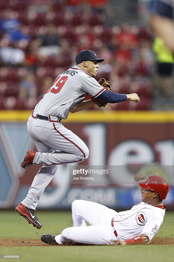 Andrelton Simmons #19 of the Atlanta Braves turns a double play against Ramon Santiago #7 of the Cincinnati Reds in the third inning of the game at Great American Ball Park on August 21, 2014 in Cincinnati, Ohio.