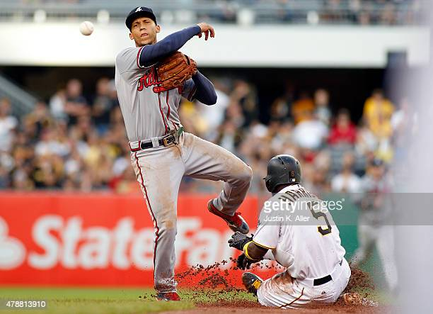 Andrelton Simmons of the Atlanta Braves turns a double play in the eighth inning against Josh Harrison of the Pittsburgh Pirates during the game at...