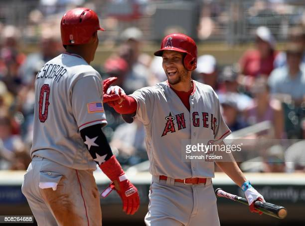 Andrelton Simmons of the Los Angeles Angels of Anaheim congratulates teammate Yunel Escobar on scoring a run against the Minnesota Twins during the...