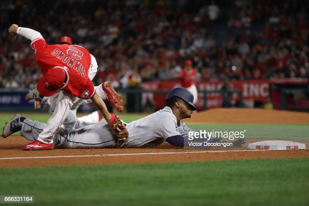 Andrelton Simmons of the Los Angeles Angels of Anaheim gets the tag on Jean Segura of the Seattle Mariners at third base during the third inning of...