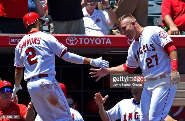 Andrelton Simmons of the Los Angeles Angels of Anaheim is greeted by Mike Trout after hitting a solo home run in the fourth inning against the Boston...