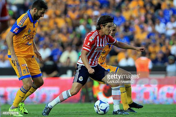 AndrePierre Gignac and Guido Pizarro of Tigres mark Carlos Fierro of Chivas during their Mexican Apertura football tournament in Monterrey Nuevo Leon...