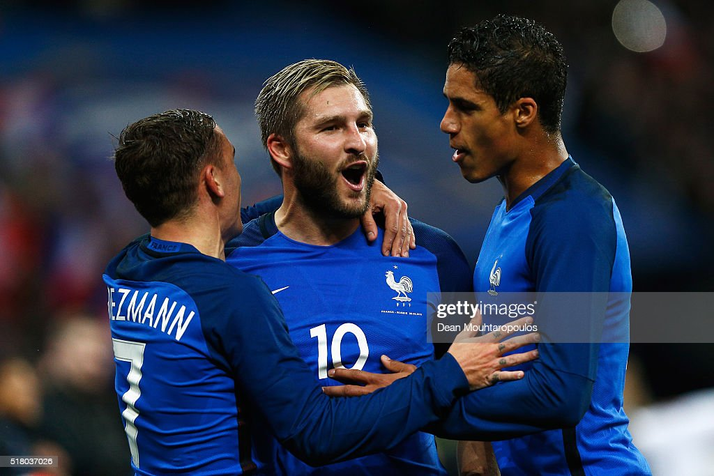 Andre-Pierre Gignac of France celebrates scoring his teams second goal of the game with Antoine Griezmann (L) and Raphael Varane (R) during the International Friendly match between France and Russia held at Stade de France on March 29, 2016 in Paris, France.