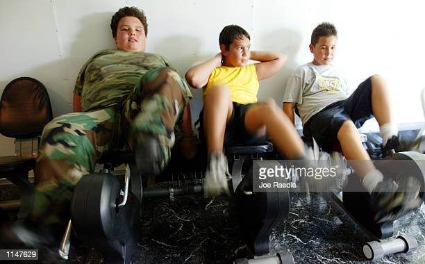 Andres Abad Mario Diaz and Mike Echevarria ride stationary bikes in the Mobile Gym For Kids which specializes training for overweight children July...