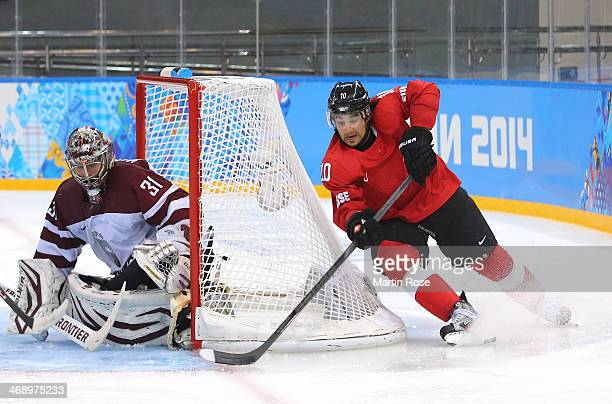 Andres Ambuhl of Switzerland shoots against Edgars Masalskis of Latvia in the third period during the Men's Ice Hockey Preliminary Round Group C game...