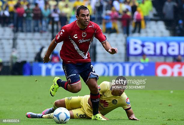 Andres Andrade of America vies for the ball with Fernando Meneses of Veracruz during their Mexican Apertura tournament football match at the Azteca...
