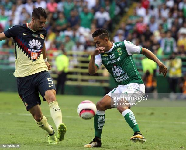 Andres Andrade of Leon vies for the ball with Guido Rodriguez of America during their Mexican Apertura tournament football match at the Nou Camp...