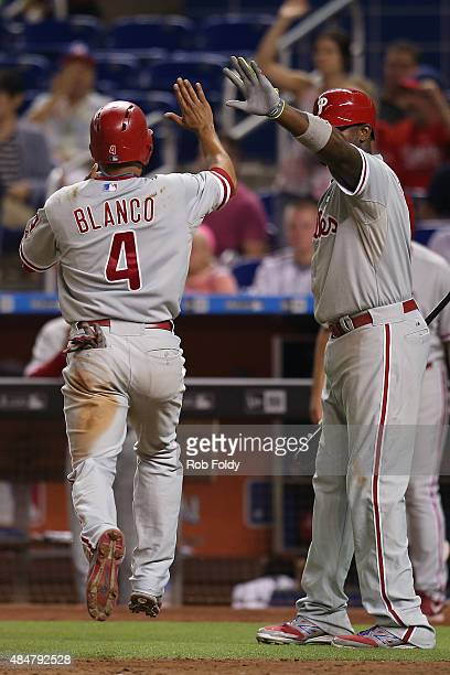 Andres Blanco highfives Ryan Howard of the Philadelphia Phillies after scoring during the fourth inning of the game against the Miami Marlins at...