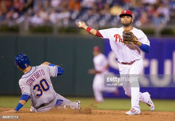 Andres Blanco of the Philadelphia Phillies attempts to turn a double play against Michael Conforto of the New York Mets at Citizens Bank Park on...