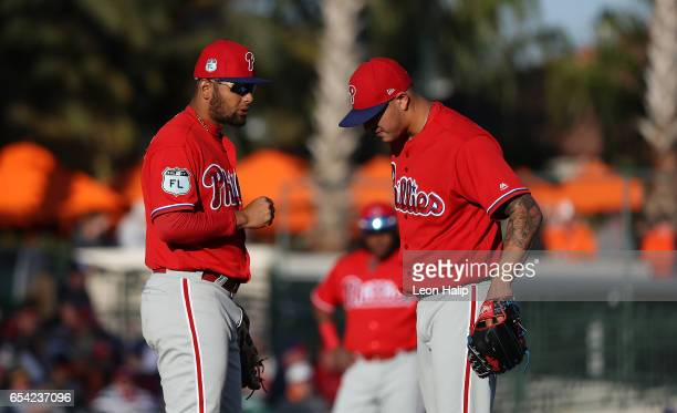 Andres Blanco of the Philadelphia Phillies talks with teammate Vince Velasquez during the second inning of the Spring Training Game against the...