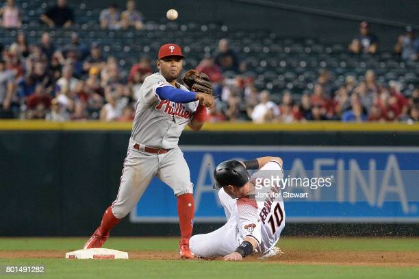 Andres Blanco of the Philadelphia Phillies turns the double play over the sliding Chris Herrmann of the Arizona Diamondbacks in the second inning at...