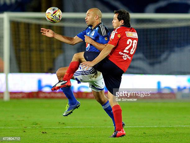 Andres Cadavid of Millonarios struggles for the ball with Hernan Hechalar of Medellin during a match between Millonarios and Medellin as part of 19th...