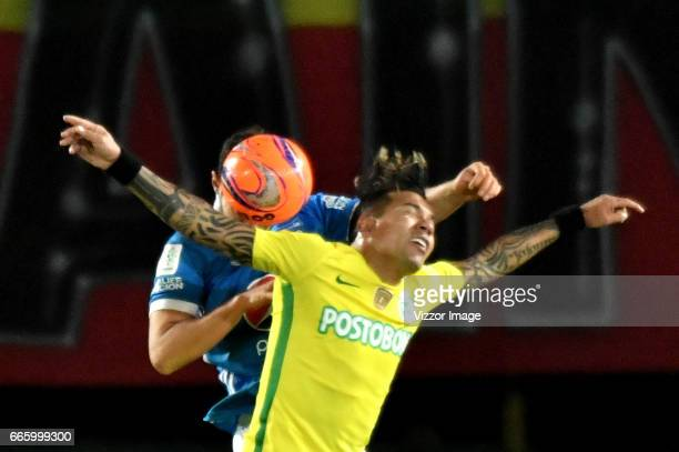Andres Cadavid of Millonarios vies for the ball with Dayro Moreno of Atletico Nacional during the match between Millonarios and Atletico Nacional as...