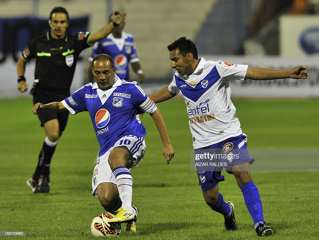 Andres Candelo (L) of Colombia´s Millonarios vies for the ball with Didi Torrico (R) of Bolivia's San Jose during their Copa Libertadores football match at Jesus Bermudez stadium in Oruro, Bolivia, on March 14, 2013.AFP PHOTO/Aizar Raldes