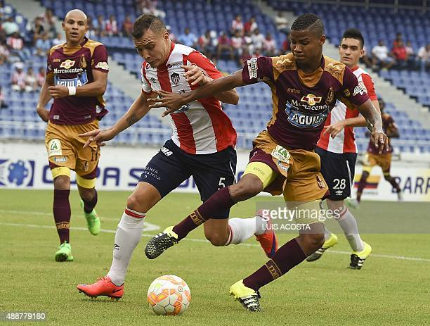 Andres Correa of Colombia's Junior vies for the ball with Matheus Uribe of Colombia's Tolima during their 2015 Sudamericana Cup football match held...