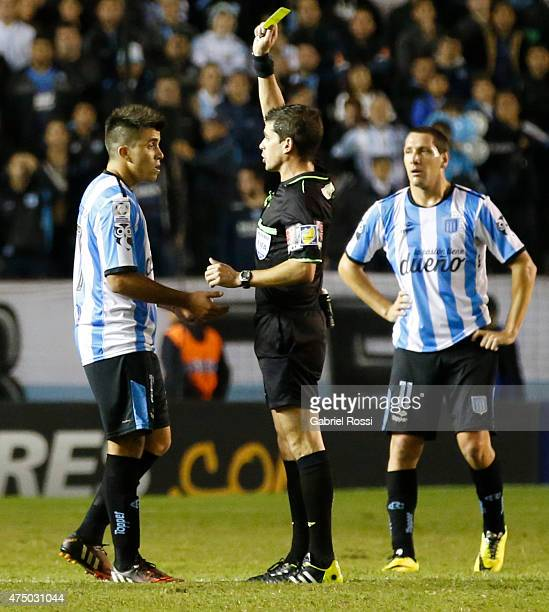 Andres Cunha referee shows a yellow card to Marcos Acuña of Racing Club during a second leg match between Racing Club and Guarani as part of quarter...