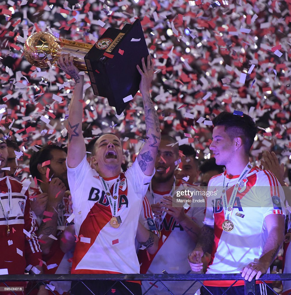 Andres D'Alessandro and Sebastian Driussi of River Plate celebrate with the trophy after winning the Recopa Sudamericana 2016 during a second leg...