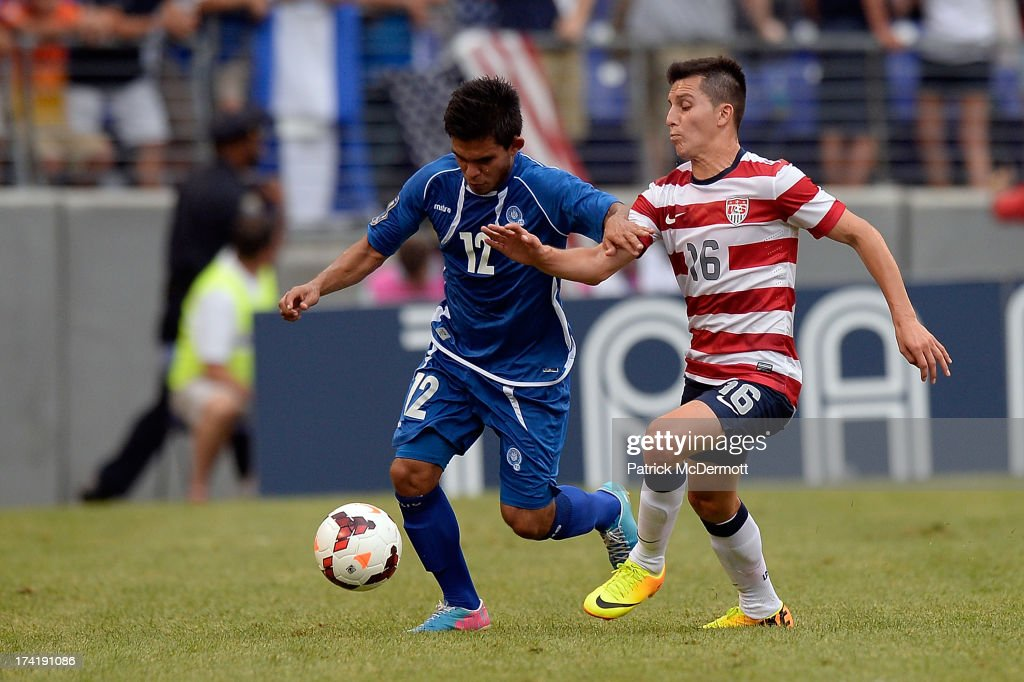 Andres Flores Mejia #12 of El Salvador battles for the ball against Jose Torres #16 of the United States during the 2013 CONCACAF Gold Cup quarterfinal game at M&T Bank Stadium on July 21, 2013 in Baltimore, Maryland.