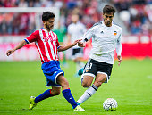 Andres Gomes of Valencia CF duels for the ball with Nacho Cases of Sporting Gijon during the La Liga match between Sporting Gijon and Valencia CF at...