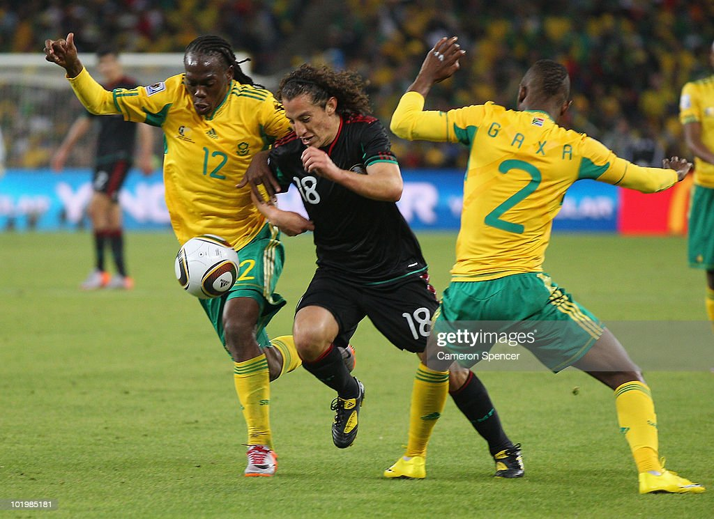 Andres Guardado of Mexico breaks through challenges from Reneilwe Letsholonyane and Siboniso Gaxa of South Africa during the 2010 FIFA World Cup...