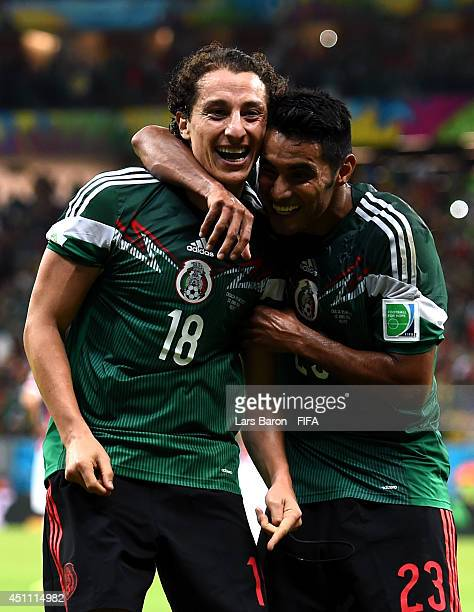 Andres Guardado of Mexico celebrates scoring his team's second goal with his teammate Jose Juan Vazquez during the 2014 FIFA World Cup Brazil Group A...
