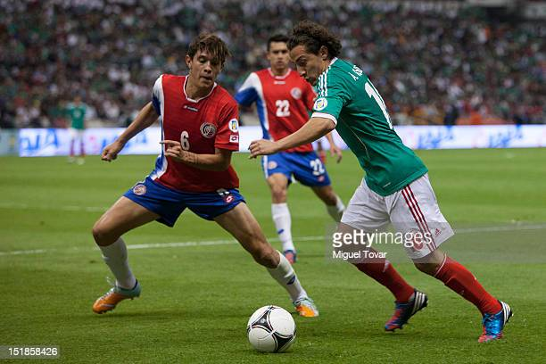 Andres Guardado of Mexico drives the ball and JoseŽ Salvatierra of Costa Rica defends during a match between Mexico and Costa Rica as part of the...