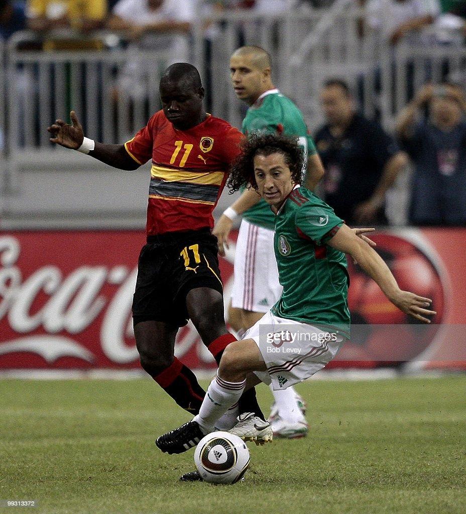 Andres Guardado #18 of Mexico keeps the ball away from Avelino Eduardo Antonio #11 of Angola at Reliant Stadium on May 13, 2010 in Houston, Texas.