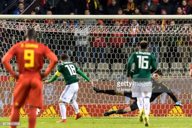 Andres Guardado of Mexico scores a penalty against goalkeeper Thibaut Courtois of Belgium during the friendly match between Belgium and Mexico on...