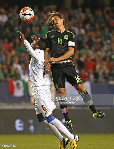 Andres Guardado of Mexicoheads the ball over Yasniel Napoles of Cuba during a match in the 2015 CONCACAF Gold Cup at Soldier Field on July 9 2015 in...