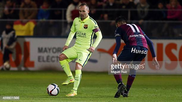 Andres Iniesa of FC Barcelona competes for the ball with Tyronne of SD Huesca during the Copa del Rey 1/16 first leg match between SD Huesca and FC...