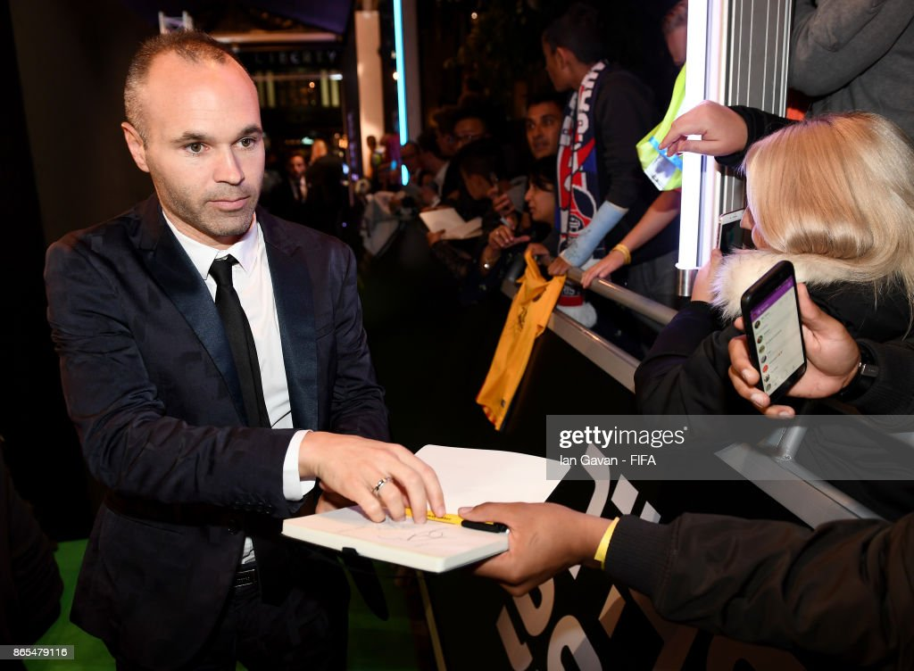 Andres Iniesta arrives and writes autographs on the green carpet for The Best FIFA Football Awards at The London Palladium on October 23, 2017 in London, England.