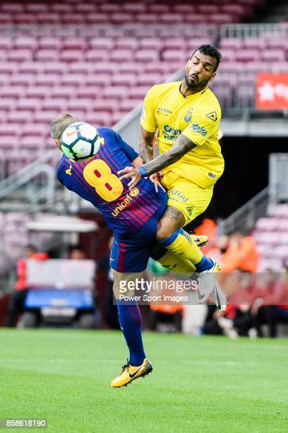 Andres Iniesta Lujan of FC Barcelona trips up with Michel Macedo of UD Las Palmas during the La Liga 201718 match between FC Barcelona and Las Palmas...