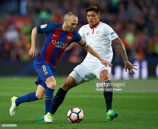 Andres Iniesta of Barcelona competes for the ball with Joaquin Correa of Sevilla during the La Liga match between FC Barcelona and Sevilla FC at Camp...
