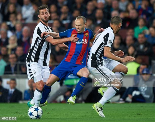 Andres Iniesta of Barcelona is tackled by Miralem Pjanic and Leonardo Bonucci of Juventus during the UEFA Champions League Quarter Final second leg...