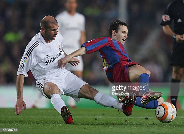 Andres Iniesta of Barcelona is tackled by Zinedine Zidane of Real Madrid during a Primera Liga match between Barcelona and Real Madrid at the Camp...