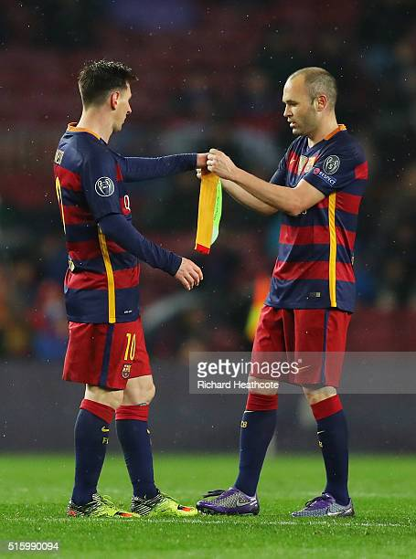 Andres Iniesta of Barcelona passes the captain's armband to his team mate Lionel Messi as he is replaced during the UEFA Champions League round of 16...