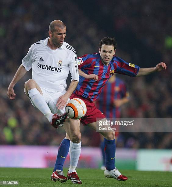 Andres Iniesta of Barcelona tackles Zinedine Zidane of Real Madrid during a Primera Liga match between Barcelona and Real Madrid at the Camp Nou...
