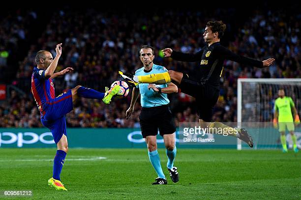 Andres Iniesta of FC Barcelona competes for the ball with Antoine Griezmann of Club Atletico de Madrid during the La Liga match between FC Barcelona...