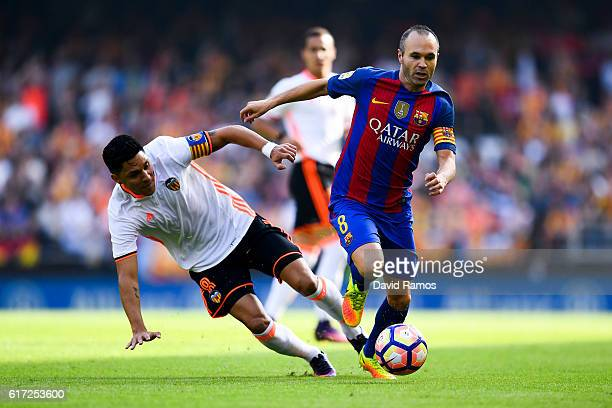Andres Iniesta of FC Barcelona competes for the ball with Enzo Perez of Valencia CF during the La Liga match between Valencia CF and FC Barcelona at...