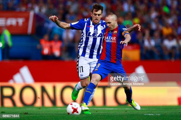 Andres Iniesta of FC Barcelona competes for the ball with Ibai Gomez of Deportivo Alaves during the Copa Del Rey Final between FC Barcelona and...