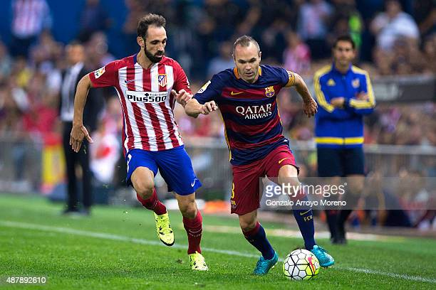 Andres Iniesta of FC Barcelona competes for the ball with Juan Francisco Torres alias Juanfran of Atletico de Madrid during the La Liga match between...