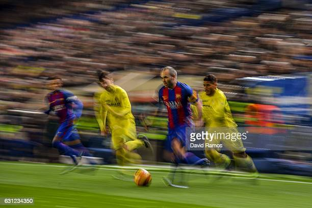 Andres Iniesta of FC Barcelona competes for the ball with Manu Trigueros and Jonathan dos Santos of Villarreal CF during the La Liga match between...